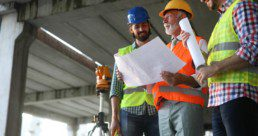Engineer, contractor, architect teamwork. Construction people talking and planning work, blueprint