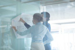 Rear view of Caucasian male and female architects discussing over blueprint in office